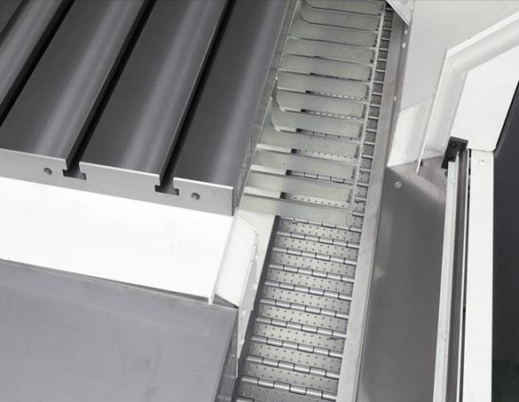 Bản lề băng tải phoi trong máy rộng bao quanh bàn máy giúp xả trơn tru khối lượng lớn phoi